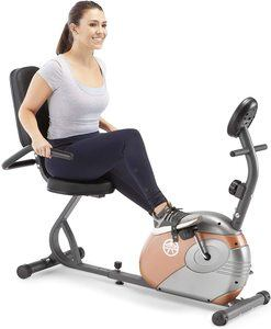 a woman in grey clothes sitting on a Marcy Recumbent Exercise bike