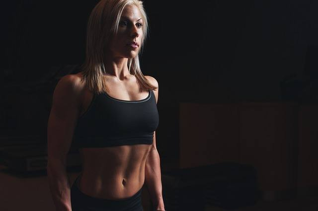 a woman in trainer shirt and black background showing her abs and fit body