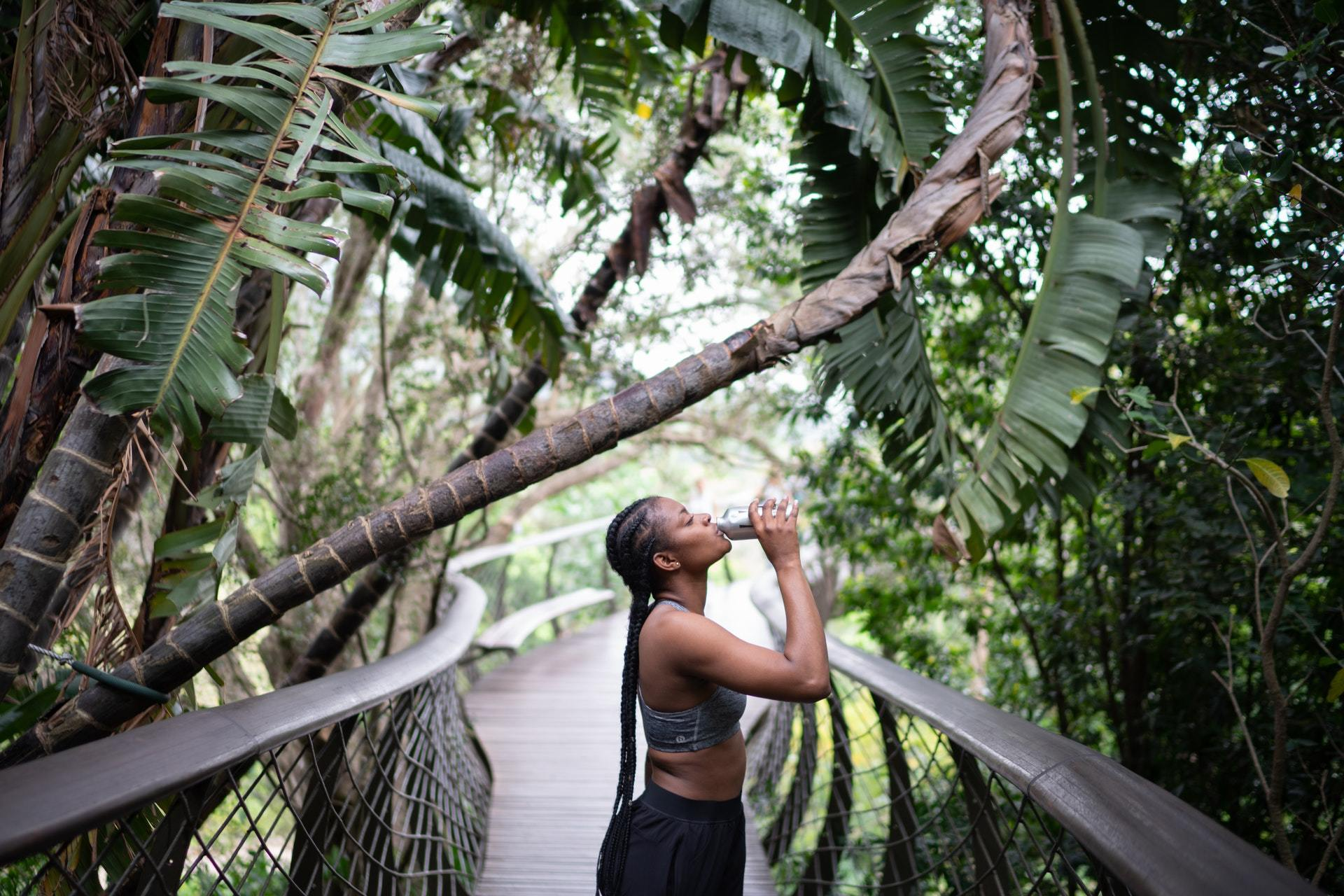 a woman drinking from a protein shaker bottle in the forest